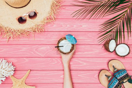 cropped shot of woman holding coconut cocktail  surrounded with various tropical travel attributes on pink wooden surface