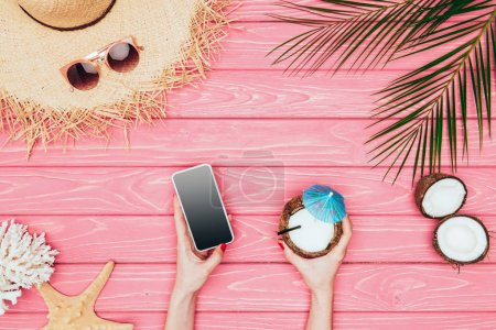 Photo for Cropped shot of woman holding smartphone and coconut cocktail on pink wooden surface - Royalty Free Image
