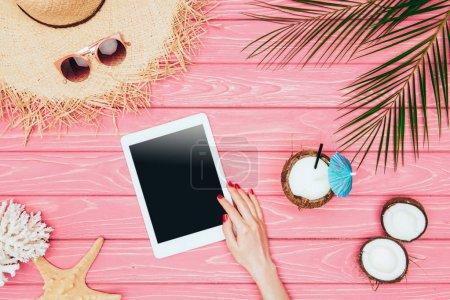 Photo pour Plan recadré de la femme en utilisant un comprimé sur une surface en bois rose avec cocktail à la noix de coco et chapeau de paille - image libre de droit