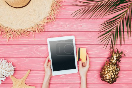 cropped shot of woman holding digital tablet with credit card on pink wooden surface with golden pineapple