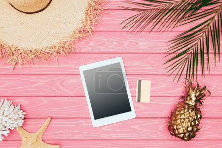 top view of digital tablet with credit card and golden pineapple on pink wooden surface