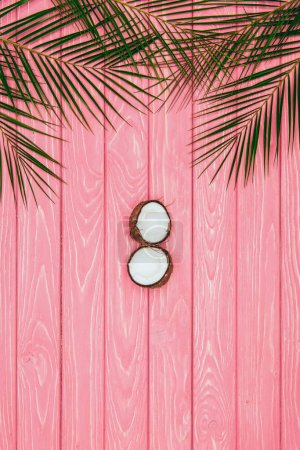 top view of halved coconut and palm leaves on pink wooden surface