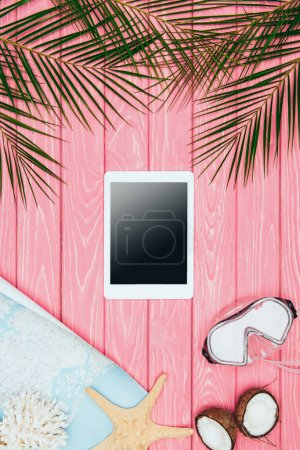 Foto de Vista superior de la tableta con mapa y máscara de buceo en superficie de madera rosa - Imagen libre de derechos