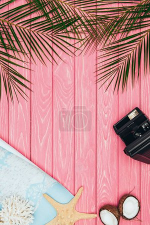 top view of map and instant print camera on pink wooden surface