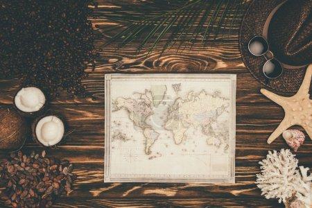 Photo pour Vue du dessus de la carte vintage entourée de divers attributs de voyage tropical sur la surface en bois - image libre de droit