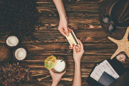 Photo pour Plan recadré de la femme payant pour cocktail de noix de coco avec carte de crédit sur la surface en bois - image libre de droit