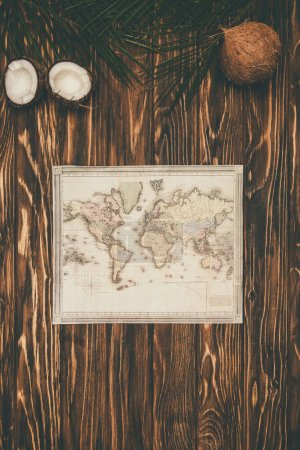 top view of vintage map and coconuts on wooden surface