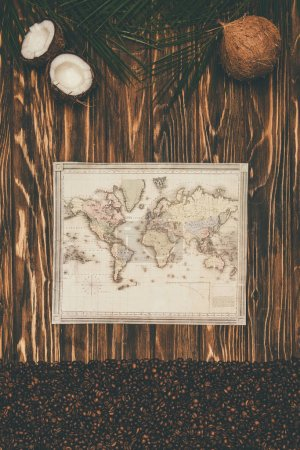 top view of vintage map with coffee beans and coconuts on wooden surface