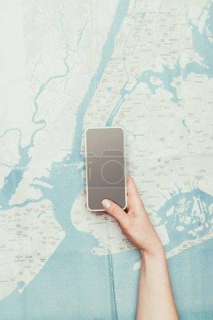 Photo pour Plan recadré de la femme en utilisant smartphone sur la carte de voyage - image libre de droit
