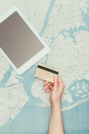 cropped shot of with tablet and credit card on travel map