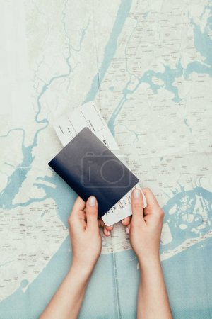 cropped shot of woman holding flight ticket and passport on travel map