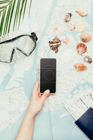 Photo pour Photo recadrée de femme avec des billets de smartphone et vol sur carte de voyage - image libre de droit