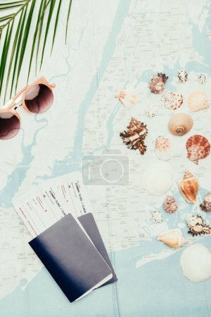 top view of flight tickets with seashells on travel map