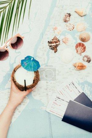 Photo pour Recadrée tir de femme avec cocktail de noix de coco et de billets d'avion sur voyage carte - image libre de droit