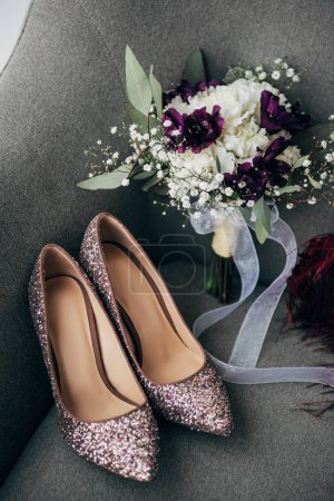 close up view of bridal shoes and bouquet for rustic wedding on armchair