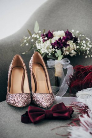 close up view of bridal shoes, grooms bow tie, wedding bouquet and feathers for rustic wedding on armchair