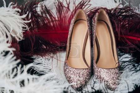 close up view of bridal shoes and decorative feathers for rustic wedding
