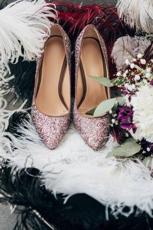 close up view of bridal shoes, wedding bouquet and feathers for rustic wedding