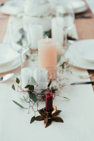 close up view of stylish table setting with candles, wineglasses and eucalyptus for rustic wedding