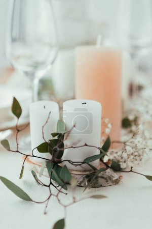 close up view of stylish table setting with candles, flowers and eucalyptus for rustic wedding