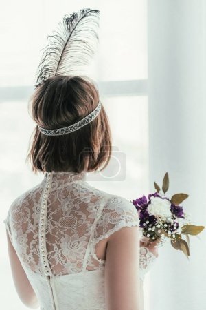 back view of bride in white dress with beautiful bridal bouquet, rustic wedding concept