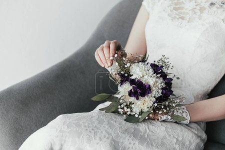 partial view of bride in white dress with beautiful bridal bouquet resting in armchair