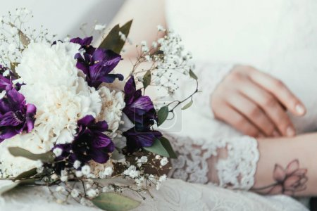 partial view of bride in white dress with beautiful bridal bouquet