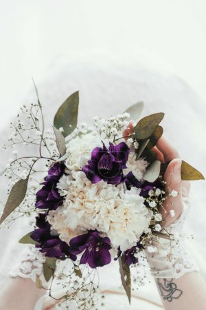 cropped shot of bride in white dress with beautiful wedding bouquet in hands