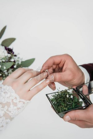 partial view of groom wearing wedding ring on bridal finger