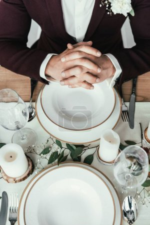 cropped shot of groom in suit sitting at served table, rustic wedding concept