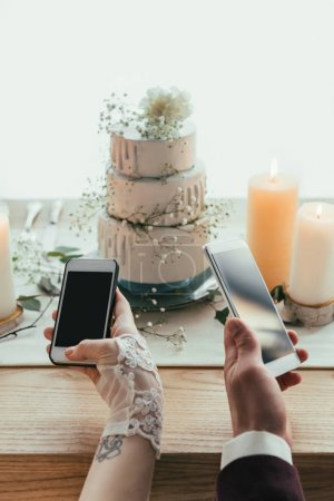 partial view of newlyweds using smartphones with blank screens while sitting at served table, rustic wedding concept