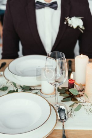 partial view of groom sitting at served table, rustic wedding concept