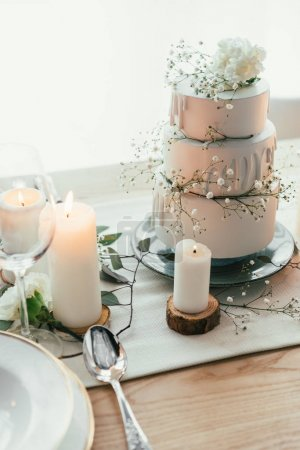 close up view of stylish table setting with candles and wedding cake for rustic wedding
