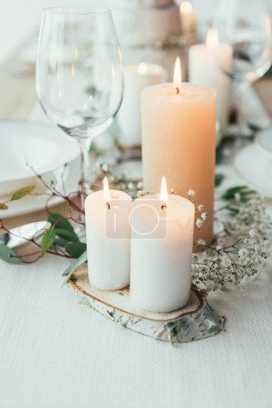 close up view of stylish table setting with candles and flowers for rustic wedding