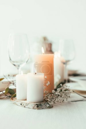 close up view of stylish table setting with candles, wineglasses and flowers for rustic wedding