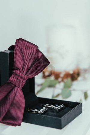 selective focus of grooms bow tie and cuffs in box for rustic wedding