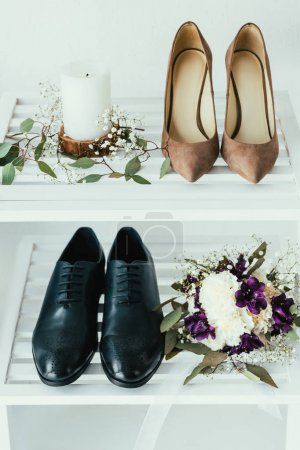 close up view of bridal and grooms shoes, candle and wedding bouquet on grey backdrop