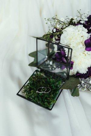 Photo pour Bouchent la vue des anneaux de mariage en boîte rustique et beau bouquet de mariée sur toile de lin blanc - image libre de droit
