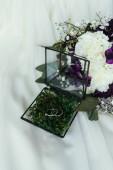bouchent la vue des anneaux de mariage en boîte rustique et beau bouquet de mariée sur toile de lin blanc