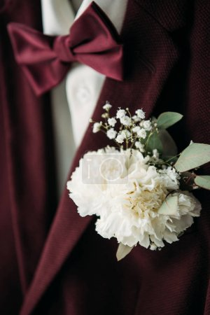 close up view of buttonhole and grooms suit with bow tie for rustic wedding