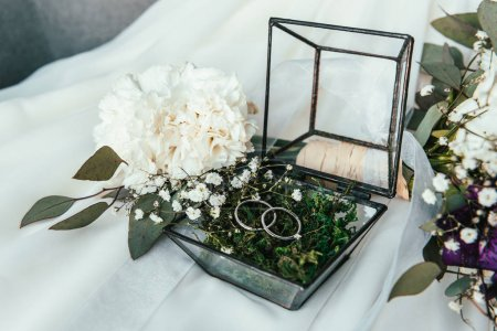 close up view of white flowers, wedding rings in rustic box with plants inside