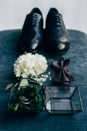 close up view of arrangement of grooms shoes, bow tie, corsage and wedding rings for rustic wedding on blue background