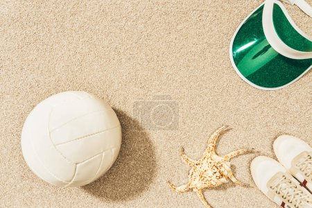 flat lay with volleyball ball, cap, sneakers and sea star on sand
