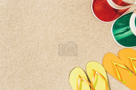 flat lay with colorful flip flops and caps arranged on sand