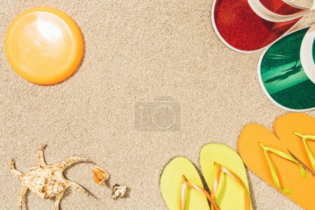 flat lay with flying disk, colorful caps, flip flops and seashells on sand