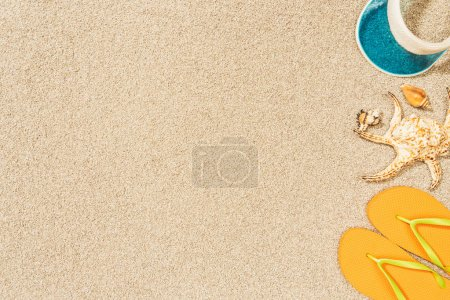 flat lay with arrangement of seashells, yellow flip flops and blue cap on sand