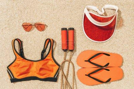 Photo pour Vue de dessus d'arrangé sauter corde, vêtements de sport, lunettes de soleil, casquette et flip flops sur sable - image libre de droit