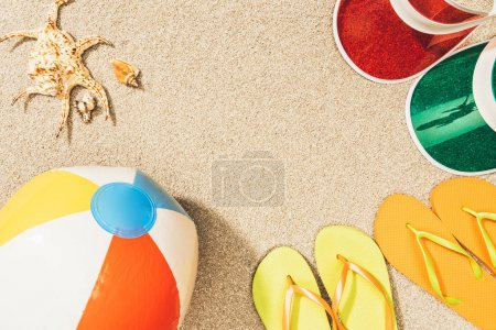 flat lay with colorful flip flops, beach ball, seashells and caps arranged on sand