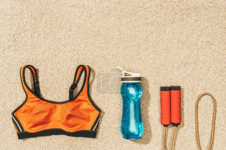 top view of arranged sportswear, skipping rope and water bottle on sand