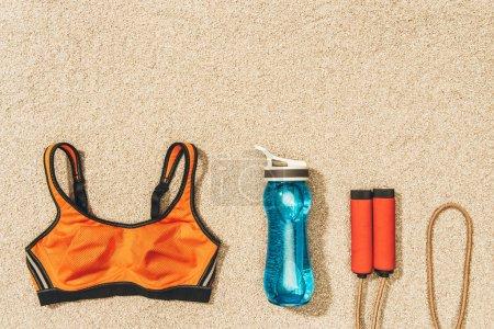 Photo pour Vue de dessus du sportswear arrangé, sauter corde et bouteille d'eau sur le sable - image libre de droit